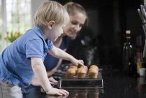 Mother and son waiting for freshly baked muffins to cool — Stock Photo