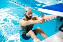 Homme dans la piscine en tenant le bloc de départ — Photo de stock