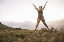 Плюс размер женщина на горы носить спортивная одежда делает звезды прыгать в воздухе — стоковое фото
