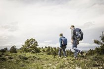 Father and teenage son hiking through landscape, Cody, Wyoming, USA — Stock Photo