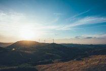 Por do sol sobre turbinas eólicas na paisagem rolante — Fotografia de Stock