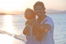 Пара объятий на пляже на закате, мужчина смотрит в камеру и улыбается — стоковое фото
