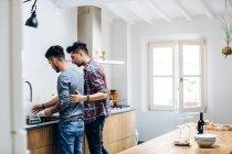 Männlichen Partner in Küche, neben Waschbecken — Stockfoto