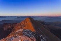 Paysage de montagnes ensoleillées avec les lointaines montagnes couronnées de neige — Photo de stock