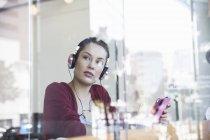 Giovane donna che si siede nella caffetteria, indossare le cuffie, che tiene compressa digitale — Foto stock