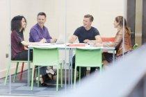 Equipo de diseño de lluvia de ideas en la mesa de la sala de juntas del estudio de diseño - foto de stock