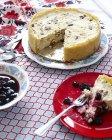 Bodegón de cheesecake en el plato con una taza de arándanos - foto de stock