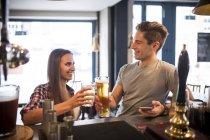 Young couple raising a toast at city bar — Stock Photo