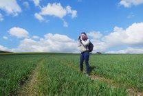 Jovem mulher em pé no campo, tirando fotos da paisagem — Fotografia de Stock