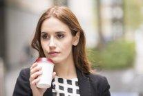 Retrato de mulher segurando copo de café descartável olhando para longe — Fotografia de Stock
