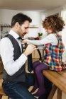 Side view of girl tying father tie in kitchen — Stock Photo