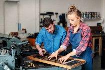 Jeune artisan et artisan regardant des lettres de presse dans un atelier d'art du livre — Photo de stock