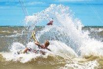 Man in sea kite surfing, splashing — Stock Photo