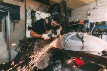 Metalworker grinding metal in forge workshop — Stock Photo