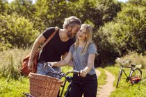 Portrait of couple with bicycles laughing on rural dirt track — Stock Photo