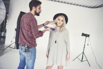 Мужчина-фотограф настраивает волосы модели на белом фоне студии — стоковое фото