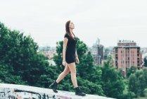 Giovane donna in mini abito camminare sul muro sopra la città — Foto stock
