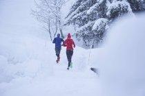 Vista posteriore del maschio e femmina runners che corrono in pista nella neve profonda — Foto stock