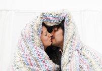 Coppie baciare sotto coperta piumone — Foto stock