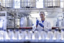 Trabajador inspeccionando botella de agua en la línea de producción en la fábrica de agua de manantial - foto de stock