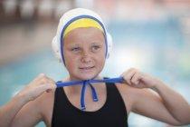 Портрет школьницы, играющей в водное поло, закрепляющей шапку — стоковое фото