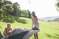 Дві молоді жінки друзі, розгортаючи намет — стокове фото
