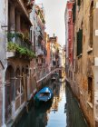 Buildings and rowboats on urban canal — Stock Photo