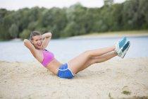 Mujer joven haciendo calentamiento ejercicios en lakeside - foto de stock