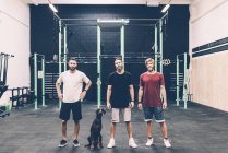 Портрет трех тренеров и собаки в тренажерном зале — стоковое фото
