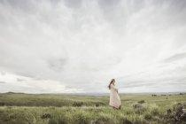 Молодая женщина, завернутые в розовый одеяло, глядя на пейзаж, Коди, Вайоминг, США — стоковое фото