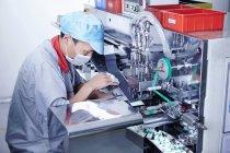 Trabajador en la fábrica de baterías de cigarrillos electrónicos, Guangdong, China - foto de stock
