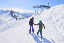 Rear view of girl and brother holding hands on ski slope, Gstaad, Switzerland — Stock Photo