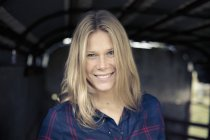 Portrait of young woman with long blond hair in barn — Stock Photo
