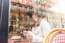 Вид из окна молодой женщины, чтение смартфон в кафе, Париж, Франция — стоковое фото