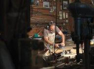 Boat builder sanding wood in workshop — Stock Photo