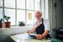 Senior craftsman holding pencil and looking at clipboard in print workshop — Stock Photo