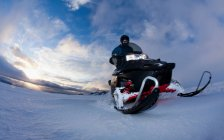 Man driving snowmobile in snowy field — Stock Photo