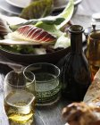 Bottle and glasses of apple cider on table with salad bowl — Stock Photo