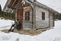Young man reading map sitting outside log cabin in winter, Elmau, Bavaria, Germany — Stock Photo