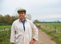 Farmer walking in country lane — Stock Photo