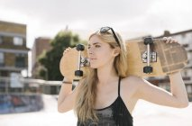 Joven mujer skater con patineta en hombros en skatepark - foto de stock