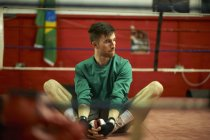 Young man exercising in boxing gym, stretching — Stock Photo