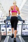Woman using exercise machine in gym — Stock Photo