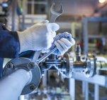 Обрізаний знімок інженера в захисні рукавички, регулюючи і кріплення машина — стокове фото