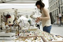 Woman looking at jewelry on market stall, Milan, Italy — Stock Photo