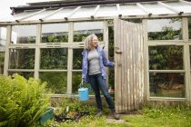 Mature woman carrying watering can opening greenhouse — Stock Photo