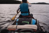 Woman canoeing on lake, rear view — Stock Photo