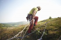 Rock climber on hillside preparing climbing rope — Stock Photo