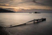Long exposure shot of pier on beach at sunset — Stock Photo