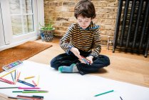 Boy sitting on floor drawing on long paper — Stock Photo